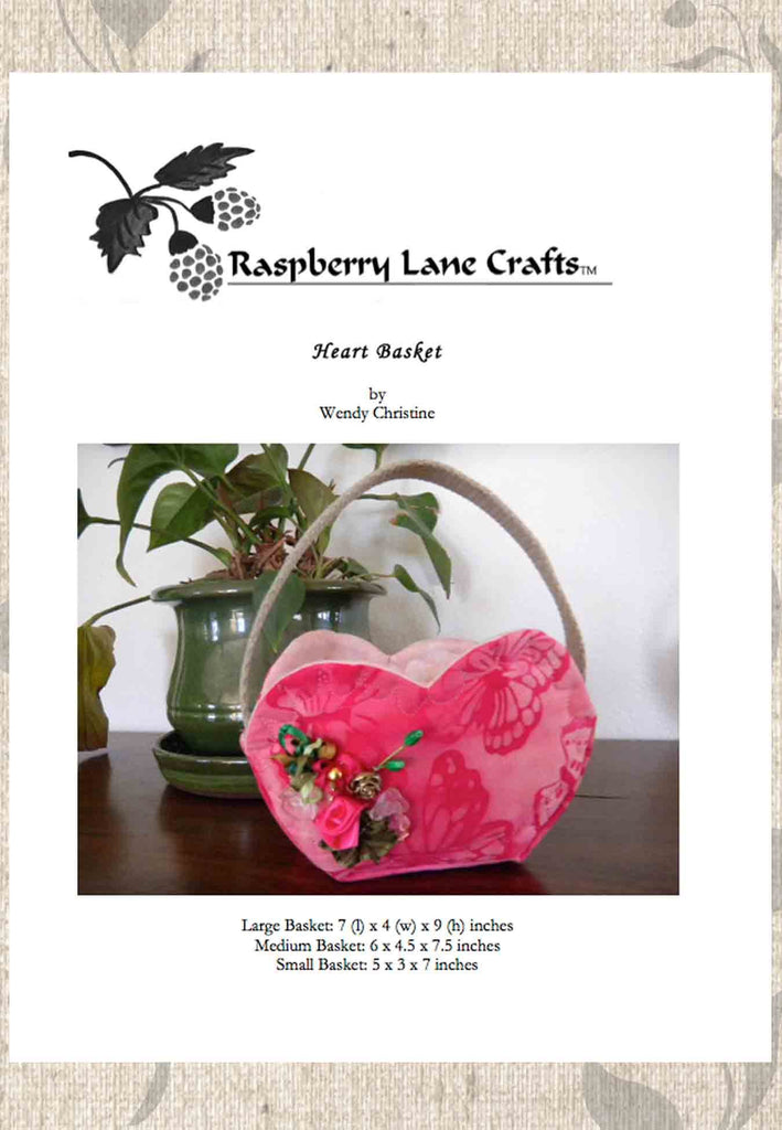 Heart Basket sewing pattern digital download front page includes the Raspberry Lane Crafts logo and finished soft heart basket made of hot pink fabric with cream handle and ribbon rose decorations.  Available for purchase at Raspberry Lane Crafts