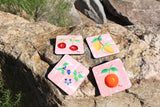 Fruit Jubilee Drink Coasters for Sale at Raspberry Lane Crafts feature cherries lemons blueberries and orange on pink.  Protect your wooden surfaces with drink coasters!