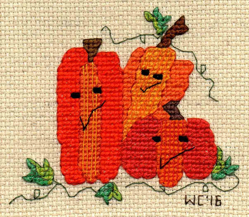 In the Pumpkin Patch cross stitch features two tall and one short orange jack-o-lantern pumpkins sitting together entwined in vines and leaves by Wendy Christine at Raspberry Lane Crafts www.raspberrylanecrafts.com