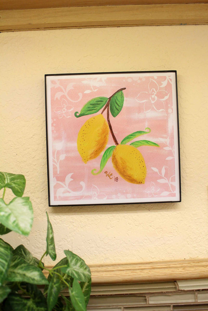 Lemon Jubilee framed print is depicted here hanging on the wall.  Two lemons with leaves on pink background.  Raspberry Lane Crafts.  The Art of Wendy Christine