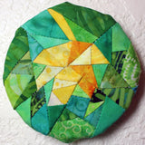 Maple Leaf Hanger sewing pattern decoration completed hanging on wall features a leaf in yellow batik fabrics and background of green batik fabrics.  Found in Leaf Hanger Pattern at Raspberry Lane Crafts.