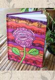 Mission Rose Hard Journal for sale features a bright Southwest pink rose on orange, yellow, and purple.  Gorgeous journal!  Raspberry Lane Crafts.