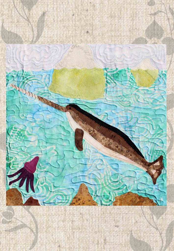 """The Narwhal"" quilt block shows a narwhal and squid underwater, icebergs floating and a rocky ocean floor. Ice Habitats Collection. Raspberry Lane Crafts. Wendy Christine"