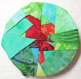 Oak Leaf Hanger sewing pattern decoration completed hanging on wall features a leaf in red batik fabrics and background of green batik fabrics.  Found in Leaf Hanger Pattern at Raspberry Lane Crafts.