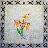 Orange Thai Orchid quilt block pattern features a trio of orange orchids with green steam and leaves, gray roots on a beige background with a border of X's and heart on the corners by Wendy Christine at Raspberry Lane Crafts