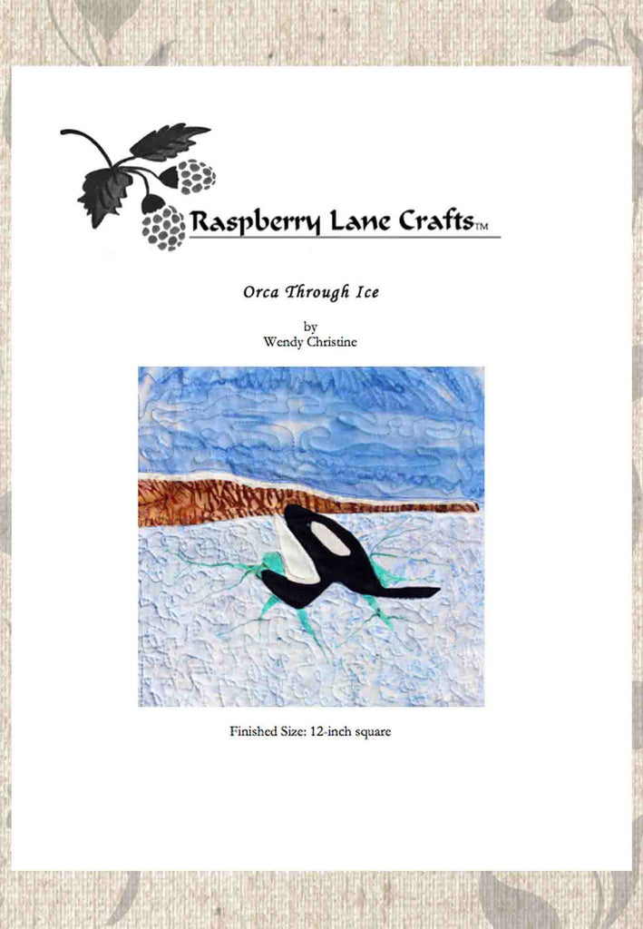 Orca Through Ice quilt block pattern digital download front page depicts a killer whale breaking white ice with aqua cracks and mountains off in the distance with blue sky.  Buy at Raspberry Lane Crafts.