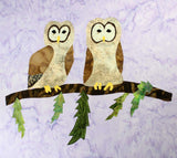 Close-up image of two tan tawny owls on a brown branch with green pine sprigs quilt block