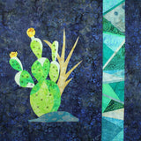 Prickly Pear with Stained Glass block features a bright green prickly pear on a dark blue background with a paper-pieced strip near the right side in shades of aqua by Wendy Christine at Raspberry Lane Crafts
