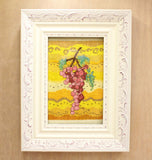 White grape decorated frame hold Rosanella Grapes in pink, red and green on a golden wavy background cross stitch.  Pattern available at Raspberry Lane Crafts.  by Wendy Christine