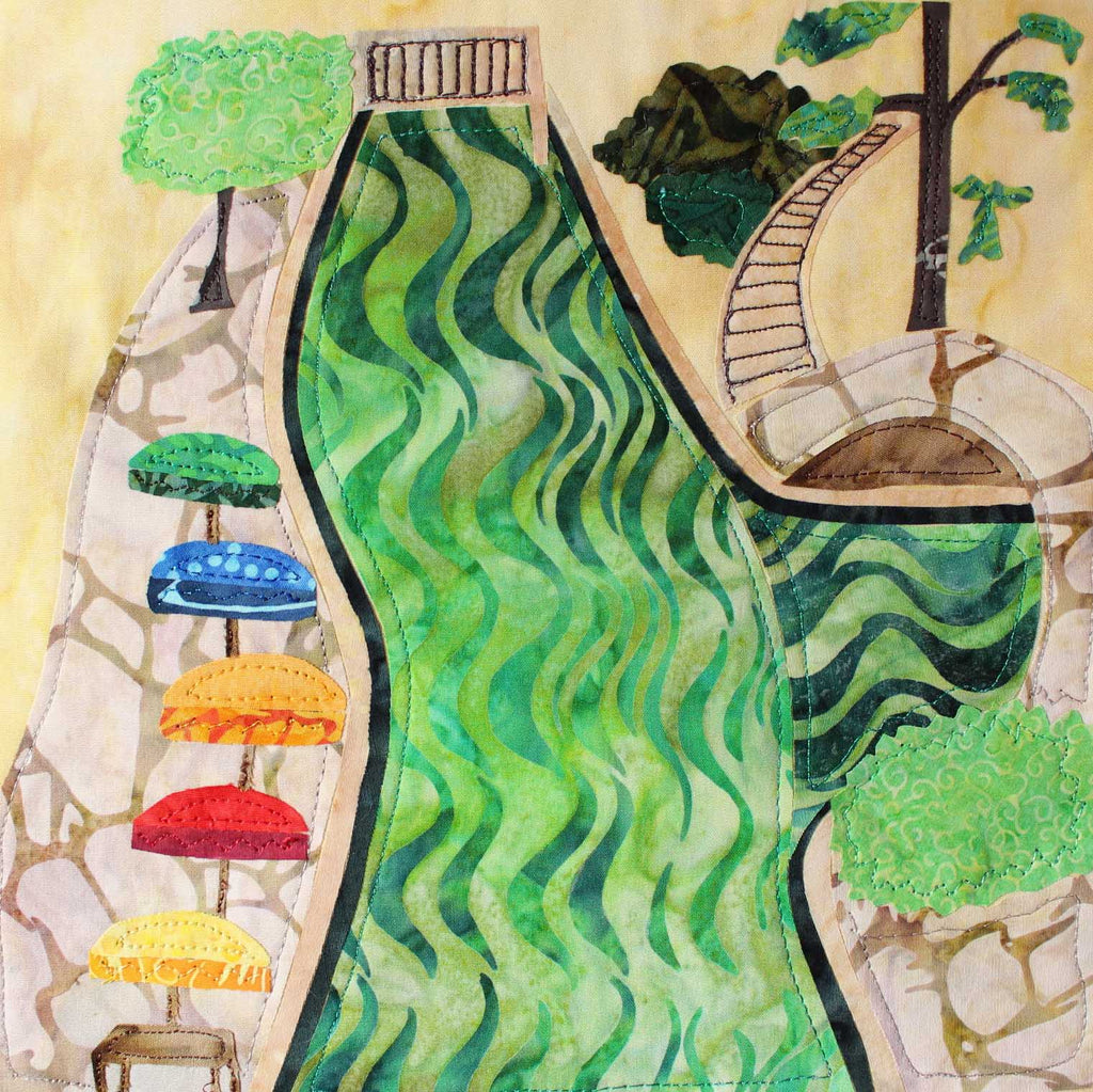San Antonio Riverwalk quilt block pattern completed sample features green water, bridges, stairways, colorful umbrellas and flagstone walkways.  Pattern available at Raspberry Lane Crafts.  Makes a 9 inch block.