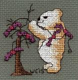 Scary Bear with Bat Lights cross stitch pattern features a tan teddy bear standing in front of a tree decorating it with a string of purple bat lights.