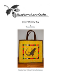 """Lizard Shopping Bag"" quilt block pattern digital download front page is pictured here in desert yellow with brown trim, centered is the lizard with a band of blocked strips of bright green, pink, orange, white and other desert colors."