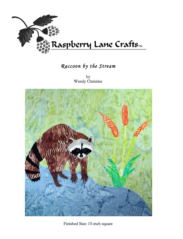 Raccoon by the Stream quilt block pattern digital download features a raccoon on all fours by a blue stream and triple cattails on a field of green fabric.  Buy at Raspberry Lane Crafts.  Mountain Habitats Collection