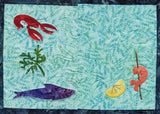Seafood Placemat features seaweed, a purple fish, red lobster, lemon and skewered shrimp.  Design by Wendy Christine at Raspberry Lane Crafts. Quilted pattern part of Dinner-On-Us Placemats.