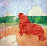 """Seashore of the Walrus"" quilt block features a long-tusked walrus on a sandy beach, green water and an iceberg in background. Ice Habitats Collection. Raspberry Lane Crafts. Wendy Christine"