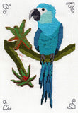 Spix's Macaw Cross Stitch pattern features a small parrot in shades of aqua on a moss-covered branch with two bromeliads.