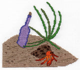 The Crab and the Bottle cross-stitch pattern features an orange hermit crab in mottled brown shell walking a pebble-strewn beach near a violet bottle and green beach grass at Raspberry Lane Crafts.