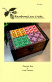 Front cover of Treasure Box cross stitch pattern printed on yellow paper features the Raspberry Lane Crafts logo and completed project.  Buy pattern at Raspberry Lane Crafts.  New May 2018