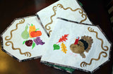 Folded up Turkey and Apples Table runner with filigree, turkey, fall leaves, and colorful fruit and gourds.