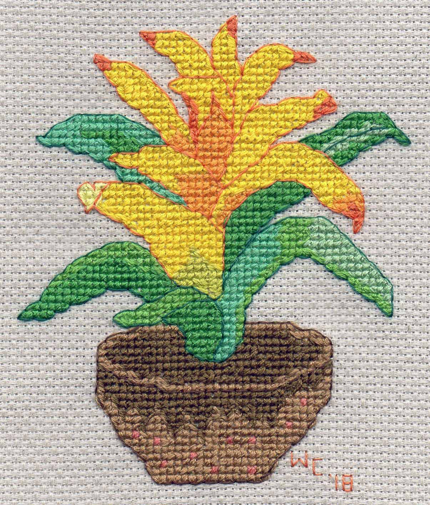 Tropical golden yellow bromeliad in pot cross stitch pattern features yellow to orange bromeliad flowering with green leaves in brown pot.  Pattern for sale at www.raspberrylanecrafts.com