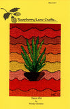 Yucca Pot cross stitch by Wendy Christine featured a potted green yucca plant with a wavy orange, red and yellow background at Raspberry Lane Crafts