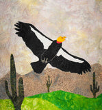 California Condor quilt block pattern photo of completed project features a black and white condor with orange head with mountains in the background and saguaro cactuses with rolling green hills.  A beautiful quilt block!  Available for purchase at Raspberry Lane Crafts.