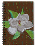 Magnolia Tree Blossom 6 x 8 spiral notebook by Wendy Christine available for purchase at Raspberry Lane Crafts features a white magnolia with green leaves on a background of dark brown with green wavy lines.