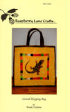 """Lizard Shopping Bag"" is pictured here in desert yellow with brown trim, centered is the lizard with a band of blocked strips of bright green, pink, orange, white and other desert colors."