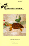 """The Desert Tortoise"" quilt block features a brown patterned back tortoise near white rocks, a senita cactus, and fairy duster blossoms."