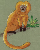 Golden Lion Tamarin cross-stitch pattern features the small monkey in shades of gold on a branch with green bromeliad from Wendy Christine at Raspberry Lane Crafts