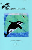 """Orca and Friend"" quilt block shows stark contrast black and white orca near an iceberg watching a penguin splash in."