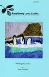 """Penguins on Ice"" quilt block features five penguins on a jutting ice floe with a rocky shore."