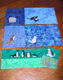 """Winter Placemats and Pillowcases"" pattern features arctic animals on blue placemats and penguins and a husky on aquamarine pillowcases. Ice Habitats Collection. Raspberry Lane Crafts. Wendy Christine"