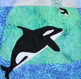 """Orca and Friend"" quilt block shows stark contrast black and white orca near an iceberg watching a penguin splash in. Raspberry Lane Crafts.  Wendy Christine"