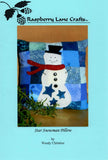 Raspberry Lane Crafts Star Snowman Pillow is an adorable white snowman with blue stars, black button on front, a red scarf and black topcoat on a background of pieced blue squares.  Perfect for winter.