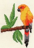 Raspberry Lane Crafts Sun Conure cross stitch pattern by Wendy Christine is a yellow and orange parrot on a branch with green leaves.