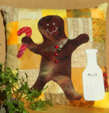"Sweet Ginger Man pillow pattern is pictured as a brown gingerbread man near a white jug that reads ""MILK"" holding a striped red candy cane on a checkered yellow background."