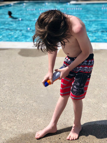 Child spraying sunscreen on his legs at the pool.