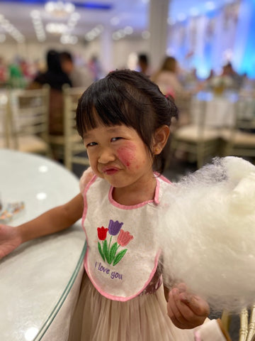 A child with eczema holding cotton candy