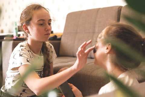 Teen girl putting a face mask on a friend.