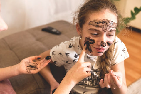 Teen girl putting on face mask.