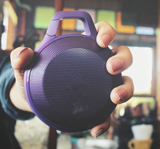 hand holding purple bluetooth speaker