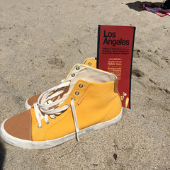 image of yellow sneakers and a map of Los Angeles on a beach