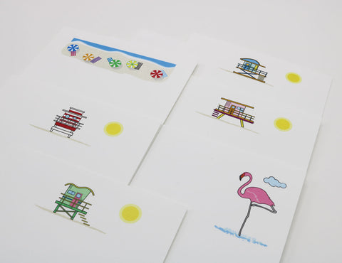 Beach themed stationery that has images of a pink Flamingo, lifeguard stations and beach umbrellas.