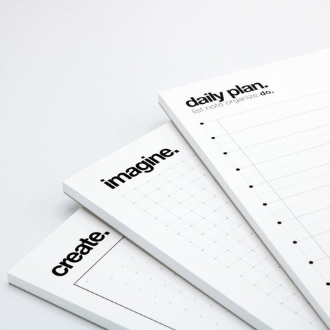 three fine-lined writing pads