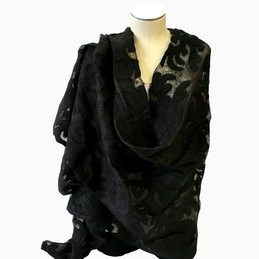 Handmade black sheer felted silk shawl, featuring traditional Kyrgyz eagle pattern, draped over coat rack | HoonArts