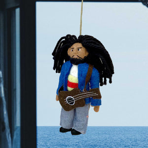 Handmade Felt Ornament of Bob Marley with Blue Jacket and Jeans, Long Black Yarn Hair, Hanging in Front of a Window Looking Out on the Ocean