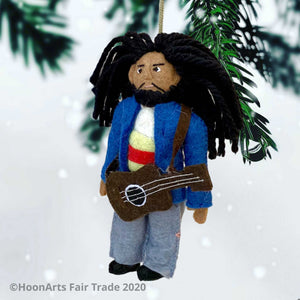 Handmade Felt Ornament-Bob Marley Dressed in Jeans and Blue Jacket with Brown Guitar, Long Black Hair and Beard from Yarn, in front of a White Background with Pine Branches in the Background