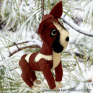 Brown and white felt boxer dog-handmade Christmas ornament, hanging from a snow-covered pine tree with long needles