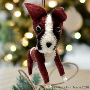 Felt Dog-Boxer, handmade Christmas ornament hanging against a background of white Christmas twinkle lights